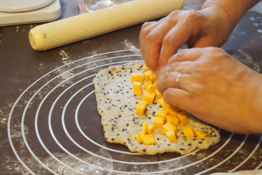 黒ごま生地にチーズを巻き込んで成形しています